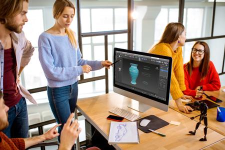 Groupe de jeunes collègues habillés avec désinvolture modélisant un projet 3d travaillant sur des ordinateurs dans le bureau moderne