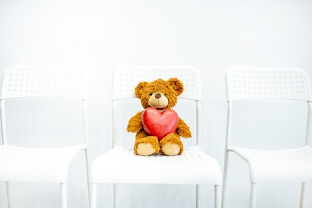 Toy teddy bear with heart shape lying on the chair on the white background Stockfoto