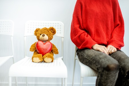 Woman sitting on the chair with toy bear waiting for the doctor on the white wall background Stockfoto