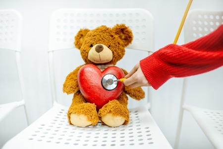 Listening with stethoscope to the heart of the toy bear in the clinic Stockfoto