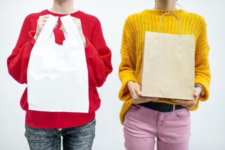 Women holding plastic and paper bags standing on the white background. Ecological in contrast to non recyclable packaging concept Stock Photo