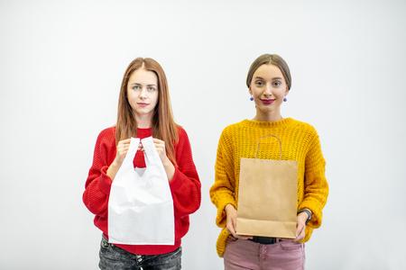Retrato de dos mujeres sosteniendo bolsas de papel y plástico de pie sobre el fondo blanco. Ecológico en contraste con el concepto de embalaje no reciclable Foto de archivo
