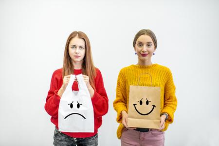 Porträt von zwei Frauen, die Plastik- und Papiertüten stehen auf dem weißen Hintergrund halten. Ökologisch im Gegensatz zu nicht recycelbarem Verpackungskonzept