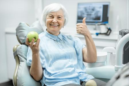 Portret van een mooie oudere vrouw met een gezonde glimlach die groene appel vasthoudt in de tandartspraktijk