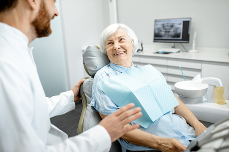 Beautiful elder woman with healthy smile sitting during the consultation with dentist at the dental office Banco de Imagens