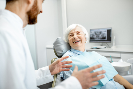 Beautiful elder woman with healthy smile sitting during the consultation with dentist at the dental office Zdjęcie Seryjne
