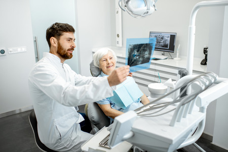 Happy elder woman during the consultation with handsome dentist showing panoramic x-ray in the dental office Foto de archivo - 114781085