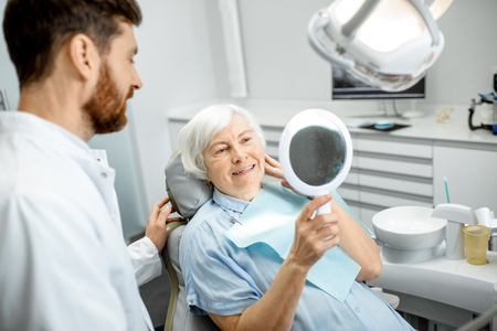 Happy elderly woman enjoying her beautiful toothy smile looking to the mirror in the dental office Foto de archivo - 114781102