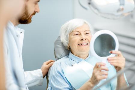 Feliz anciana disfrutando de su hermosa sonrisa con dientes mirando al espejo en el consultorio dental