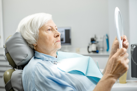 Elderly woman worried with her teeth looking on the mirror in the dental office