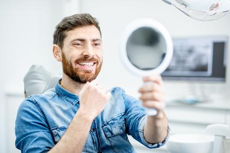 Retrato de un apuesto hombre barbudo con sonrisa saludable en el consultorio dental Foto de archivo