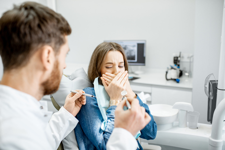 Woman with a frightened facial expression during a stomatological procedure with male doctor in the dental office