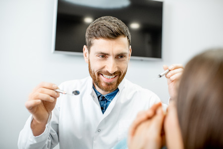Enthusiastic male dentist with crazy facial expression during the procedure in the dental office