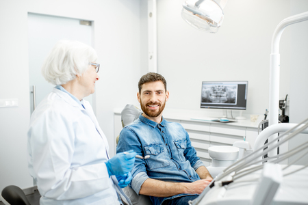 Portrait of a handsome male patient in blue shirt with elderly woman dentist in the dental office