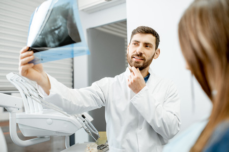 Handsome dentist checking panoramic x-ray of a jaw during the medical consultation with woman patient in the dental office Stock Photo