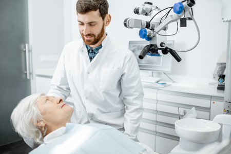 Dentist during the consultation with senior woman patient befrore a procedure in the surgery dental office with microscope Stock Photo