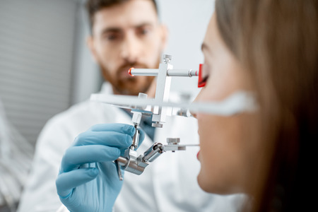 Dentist putting jaw measurement system to a young woman patient in the dental office, close-up view
