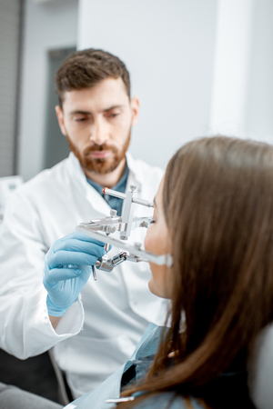 Dentist putting jaw measurement system to a young woman patient in the dental office