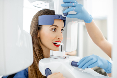 Mujer joven haciendo foto panorámica de la mandíbula sosteniendo su rostro en la máquina de rayos x Foto de archivo