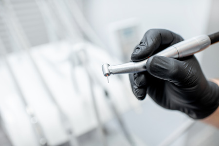 Close-up of a dental drill with nozzle in the hands in black medical gloves Banque d'images