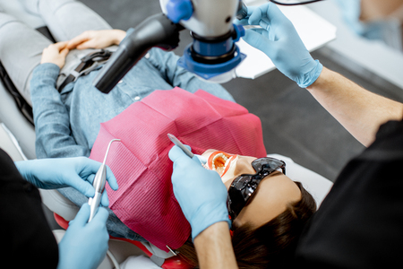 Dentists making dental examination to a young woman with professional microscope