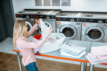 Young woman sorting clothes for washing standing in the self service laundry