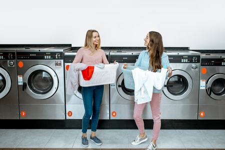 Two cheerful girlfriends standing together with baskets full of clothes in the self service laundry with washing machine on the background 版權商用圖片