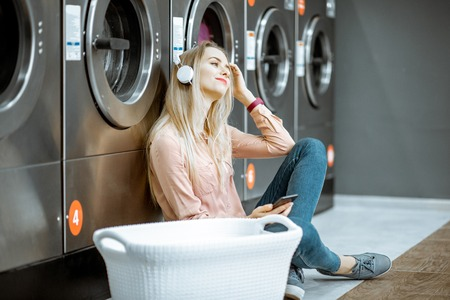 Young woman waiting for the clothes to be washed sitting on the floor and listening to the music at the self-service laundry