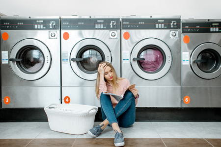 Young and sad woman waiting for the clothes to be washed sitting on the floor at the self-service laundry