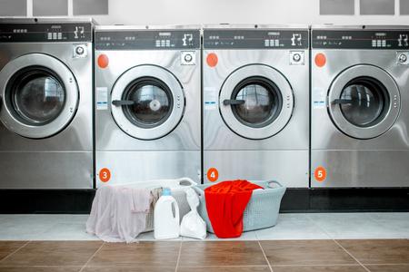 Lavadoras profesionales con cestas llenas de ropa en la lavandería de autoservicio