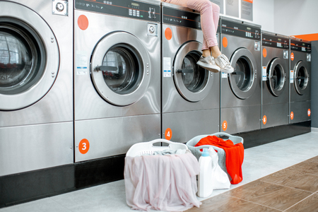 Woman sitting on the washing machine waiting for the washing at the self-service laundry with baskets full of clothes. Cropped image with no face 스톡 콘텐츠