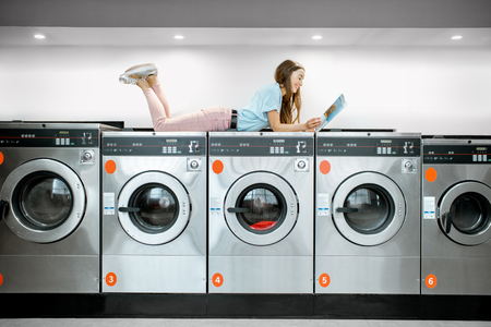 Young woman lying on the washing machiness reading some magazine while waiting for clothes washing in the self-service laundry