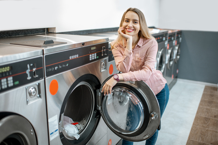 Portrait of a young smiling woman standing in the self-service public laundry