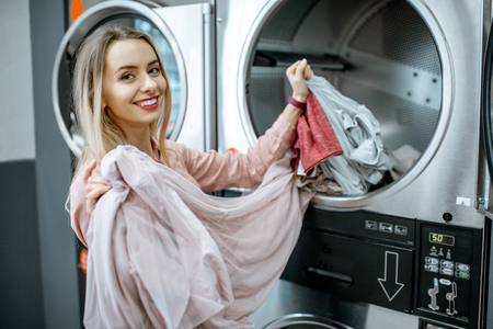 Smiling woman taking out clean and dried clothes from the drying machine in the self-service laundry