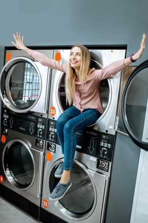 Portrait of a cheerful woman sitting on the dryer machine in the self-service public laundry