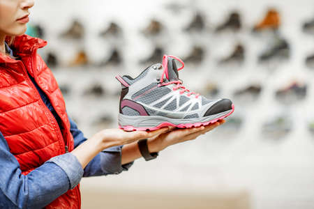 Woman holding beautiful shoes for hiking in the sport shop, close-up view Reklamní fotografie