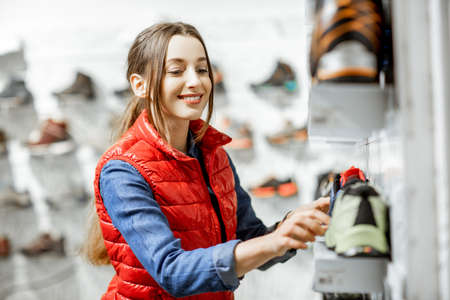 Young woman choosing trail shoes for hiking standing near the showacase of the modern sports shop Reklamní fotografie
