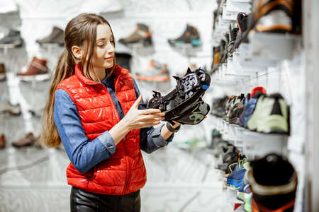 Young woman choosing snowmobile shoes for ice climbing standing near the showacase of the modern sports shop