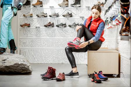 Frau, die Schuhe zum Bergwandern anprobiert, sitzt in der Umkleidekabine des modernen Sportgeschäfts