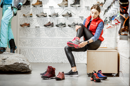 Woman trying shoes for mountain hiking sitting in the fitting room of the modern sports shop