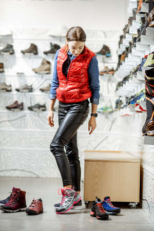 Woman trying shoes for mountain hiking sitting in the fitting room of the modern sports shop 免版税图像 - 150637602