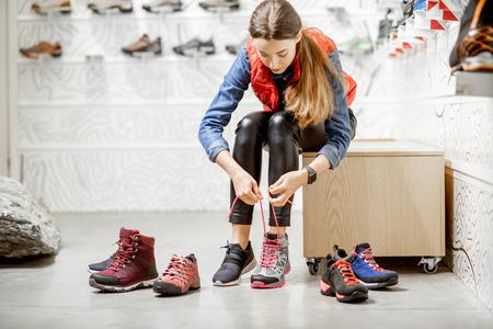 Frau, die Schuhe zum Bergwandern anprobiert, sitzt in der Umkleidekabine des modernen Sportgeschäfts Standard-Bild