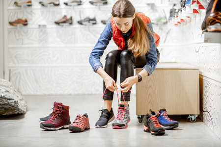 Woman trying shoes for mountain hiking sitting in the fitting room of the modern sports shop 写真素材 - 115281240