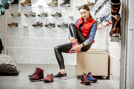 Kobieta przymierza buty do górskich wędrówek siedząc w przymierzalni nowoczesnego sklepu sportowego