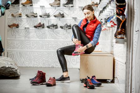 Vrouw probeert schoenen voor bergwandelingen in de paskamer van de moderne sportwinkel sports