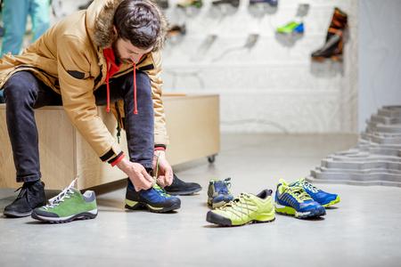 Hombre en chaqueta de invierno probándose zapatos para senderismo de montaña sentado en el probador de la moderna tienda de deportes Foto de archivo