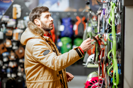 Man in winter jacket choosing mountaineer equipment in the sports shop 写真素材