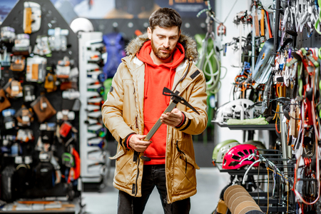 Man in winter jacket choosing mountaineer equipment holding ice axe in the sports shop 写真素材