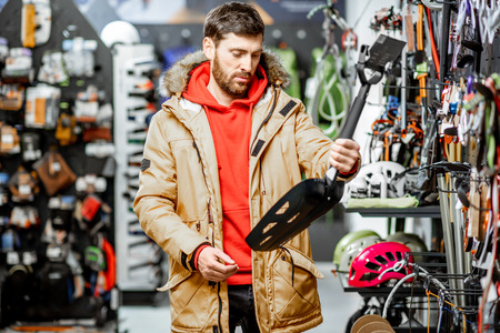 Man in winter jacket choosing mountaineer equipment holding snow shovel in the sports shop