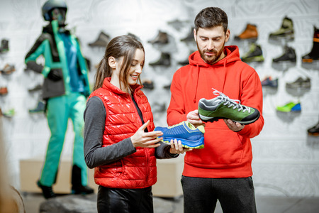 Man and woman choosing shoes for hiking standing in the modern sports shop with beautiful showcase on the background